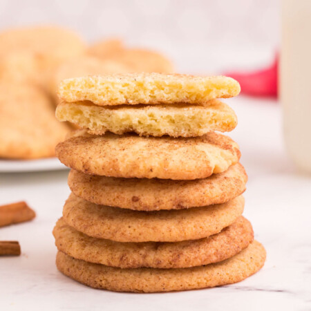 Four stacked snickerdoodles with one on top broken in half to see the interior