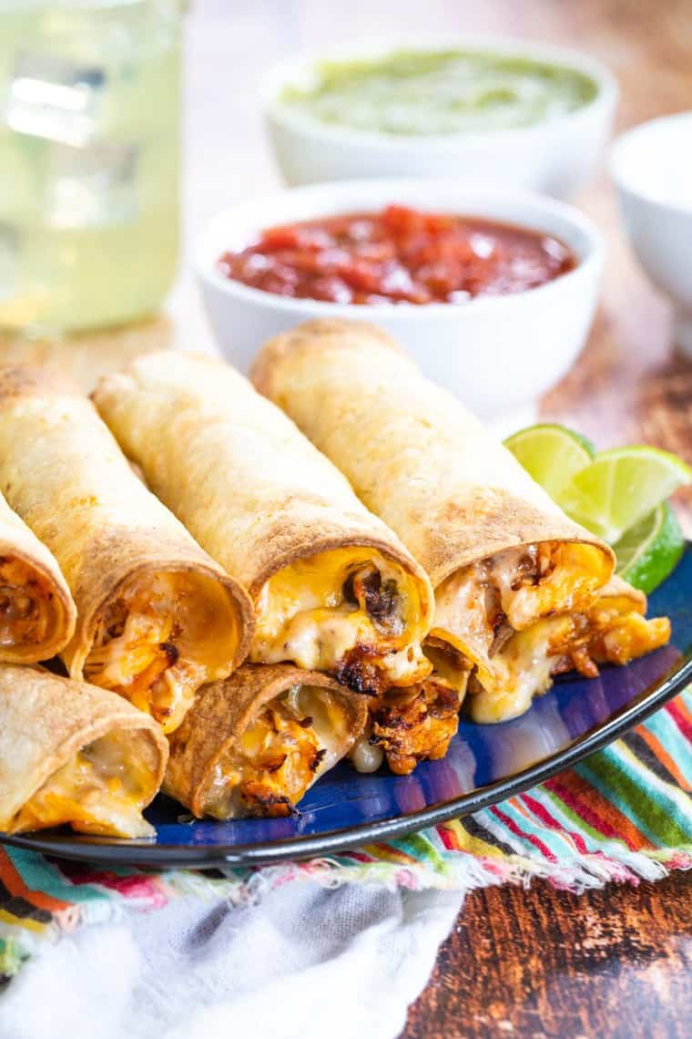 A pile of chicken and black bean taquitos on a plate with cheede oozing out