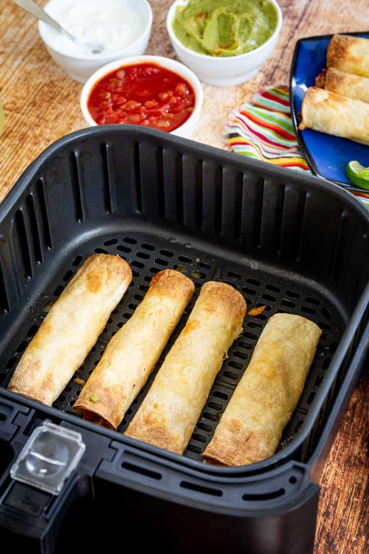 Cooked chicken taquitos in an air fryer basket