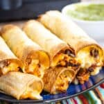 Air Fryer Chicken Taquitos with cheese oozing out stacked on a dark blue plate