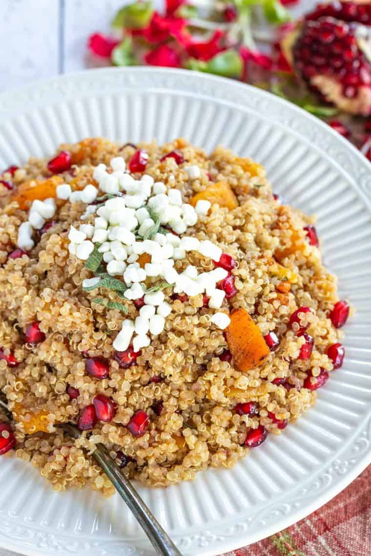 Butternut squash quinoa in a decorative serving bowl with a spoon in it