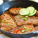 Cast iron pan with four cube steaks with a red-colored chili sauce and lime slices