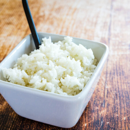 cooked white rice in a bowl on a wooden table