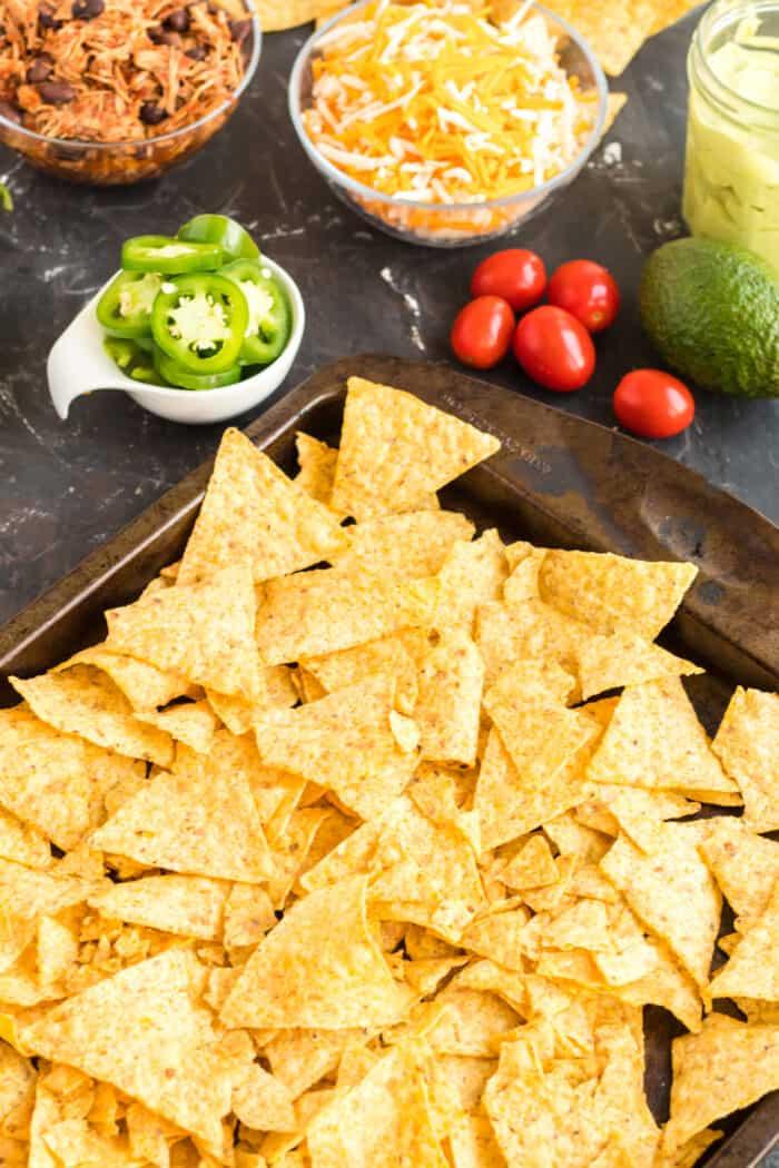 Tortilla chips spread on a baking sheet