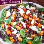 Large plate with a Pomegranate and Roasted Butternut Squash Salad drizzled with dressing