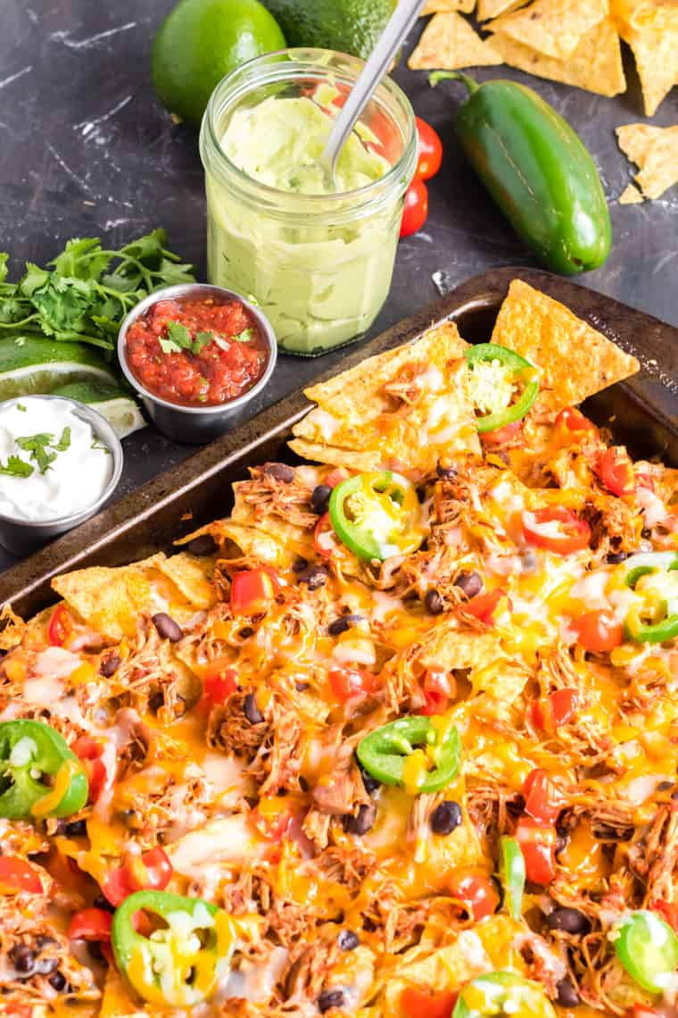 Chicken nachos on a sheet pan with small bowls of salsa, sour cream and avocado cream