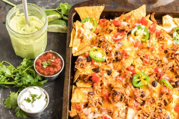 Sheet pan chicken nachos with bowls of toppings on the side