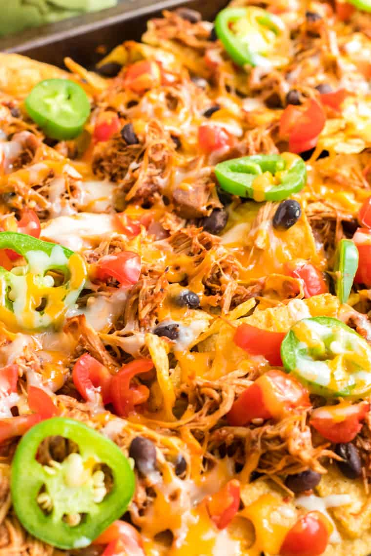 nachos topped with chicken, black beans, tomatoes, jalapenos, and melted cheese