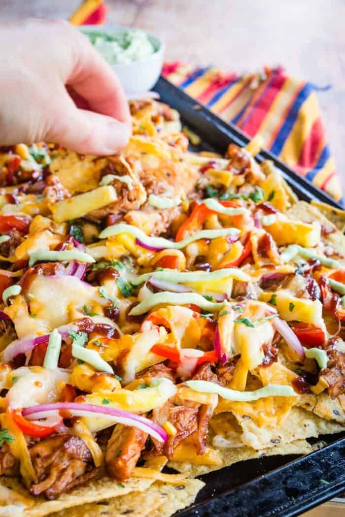 hand picking up one of the barbecue chicken nachos