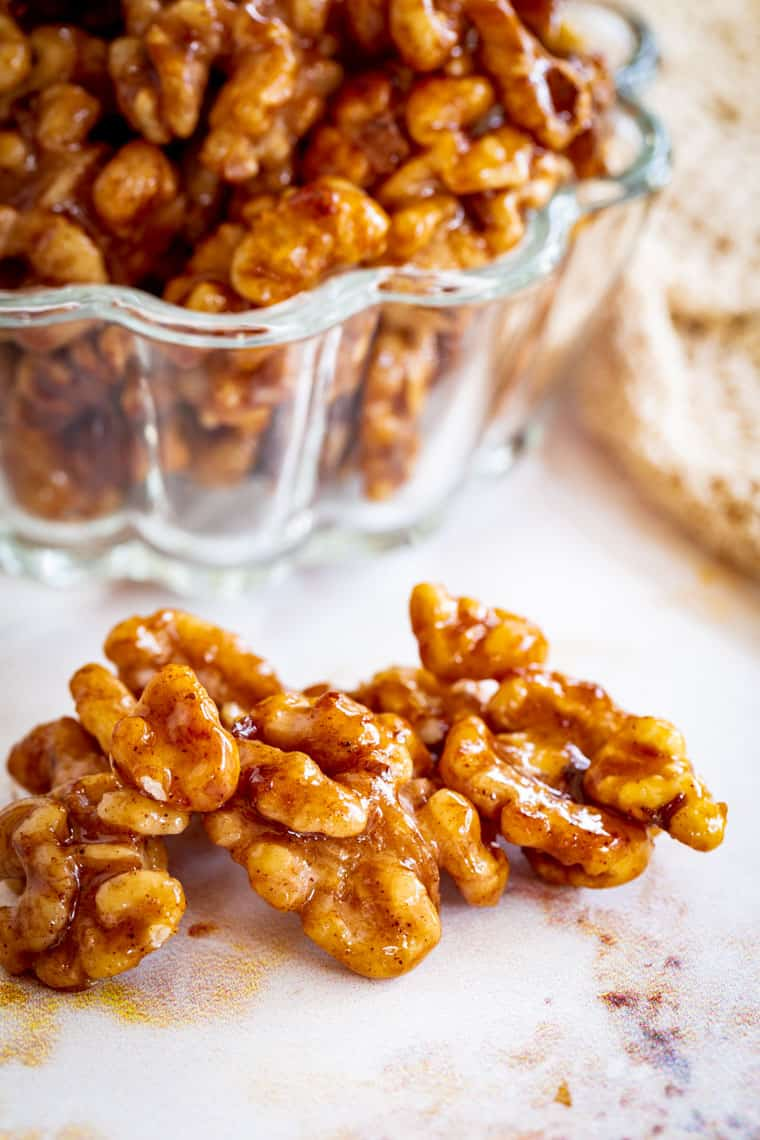 honey cinnamon glazed walnuts on a table in front of a bowl