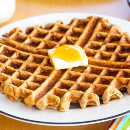 Golden brown waffle on a plate with a pat of butter and syrup