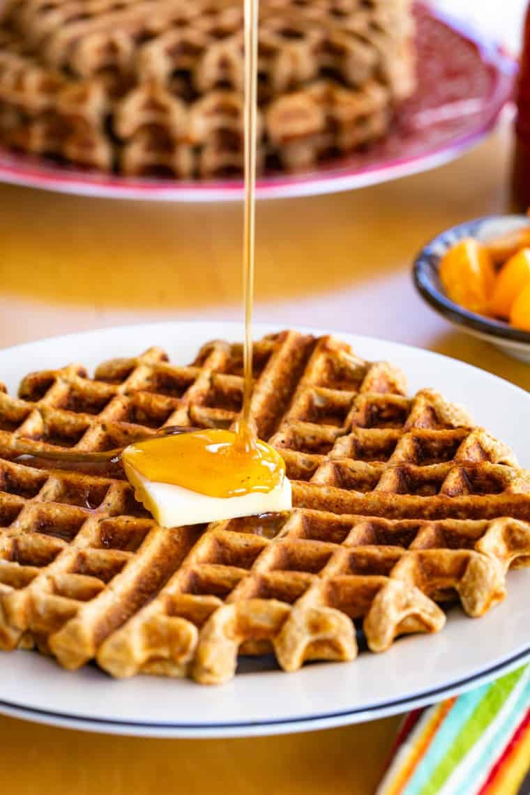 pouring syrup on a waffle with butter