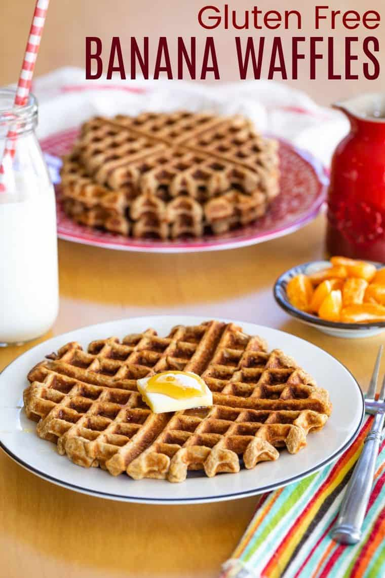 waffle on a plate with butter and syrup with a stack of more waffles on the table