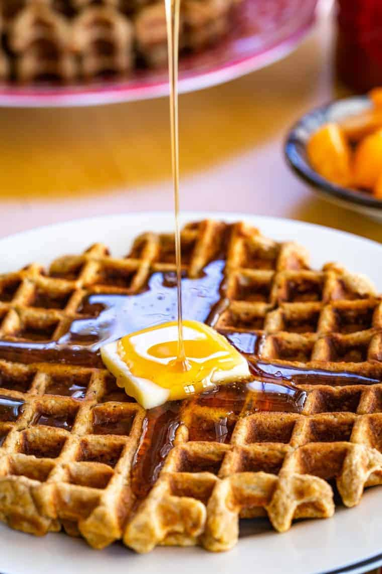 maple syrup pouring on top of a waffle