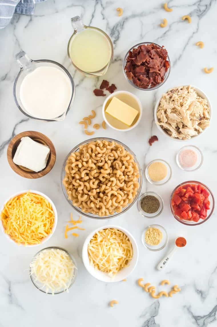 bowls and measuring cups and spoons holding elbow noodles, chicken broth, heavy cream, cream cheese, cheeses, spices, chicken, bacon, and tomatoes