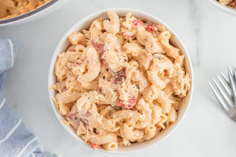 gluten free mac and cheese with bacon, chicken, and tomatoes served in a white bowl