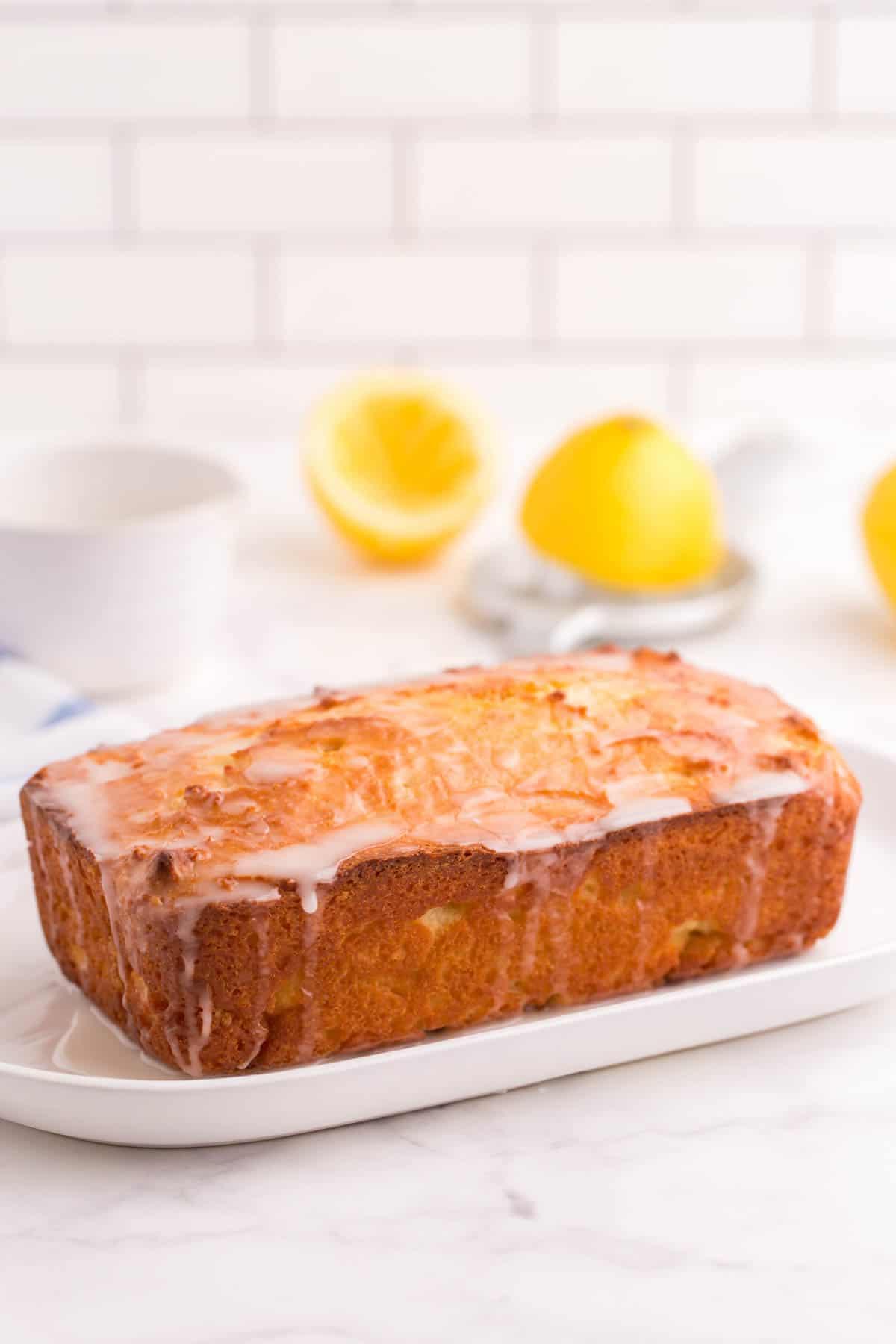 Finished glazed lemon bread on a white platter