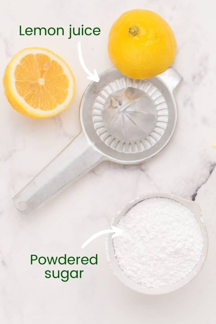 Lemon halves and a juice and a bowl of powdered sugar