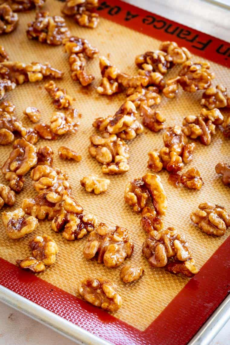 honey glazed walnuts cooling on a silicone mat on top of a baking sheet