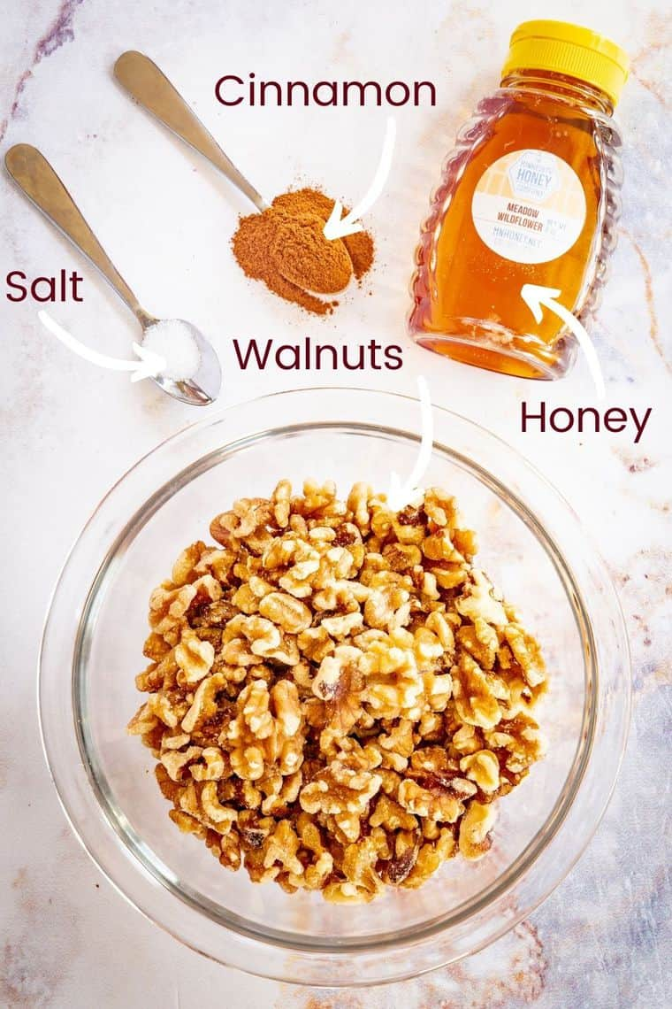 bowl of walnuts, bottle of honey, and small spoons holding cinnamon and salt
