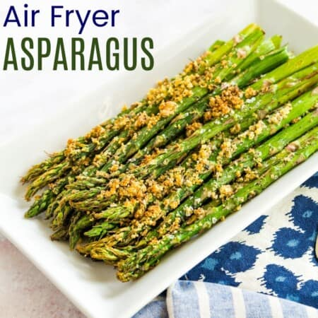 cooked asparagus with parmesan cheese crust on a white rectangular plate