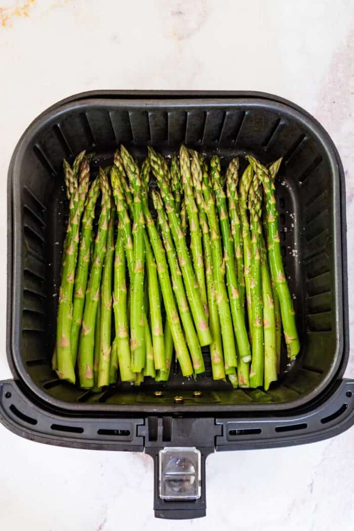 raw asparagus seasoned with salt and pepper in an air fryer basket