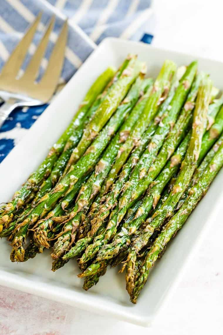simple air fryer roasted asparagus on a white rectangular plate