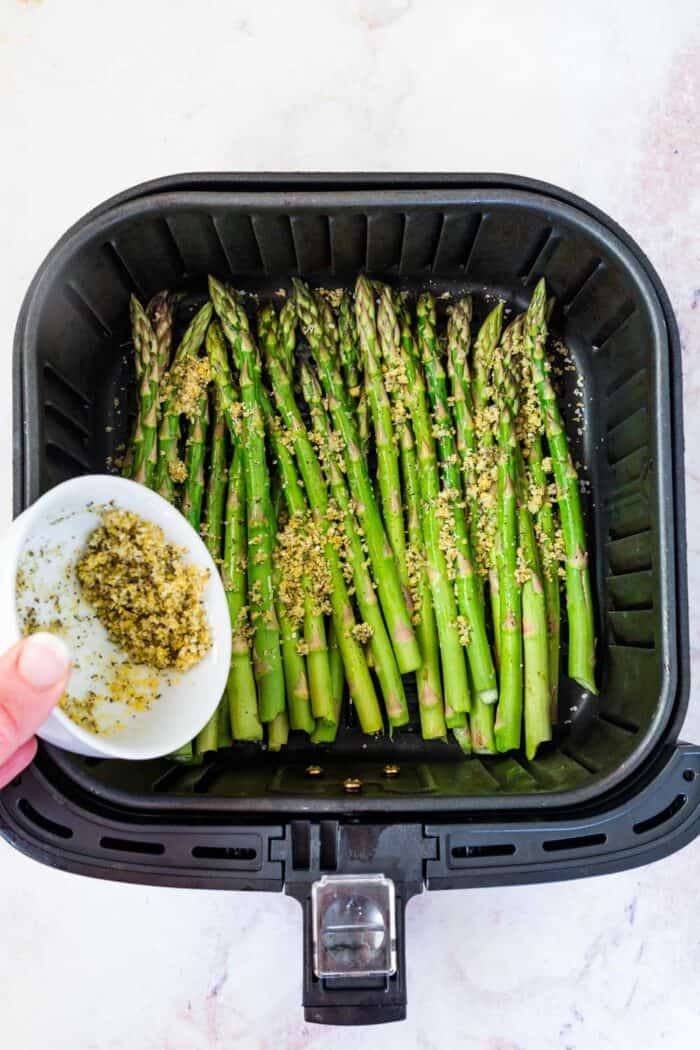 sprinkling crumb topping over raw asparagus in an air fryer basket