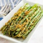 air fryer asparagus with parmesan cheese crust on a white rectangular plate