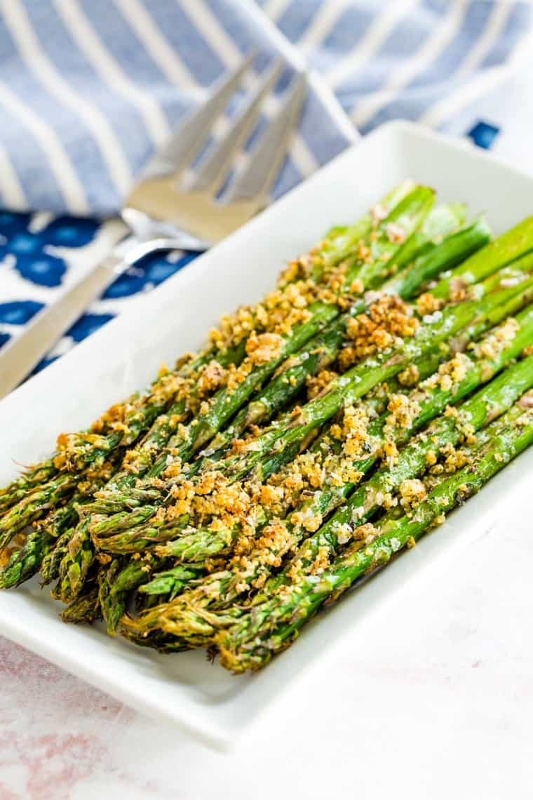 parmesan crusted air fryer roasted asparagus on a white rectangular plate
