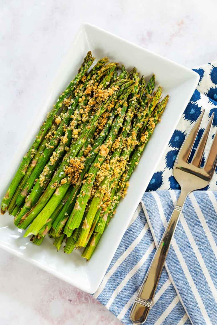 air fryer asparagus with parmesan herb crust on a white rectangular plate with a serving fork
