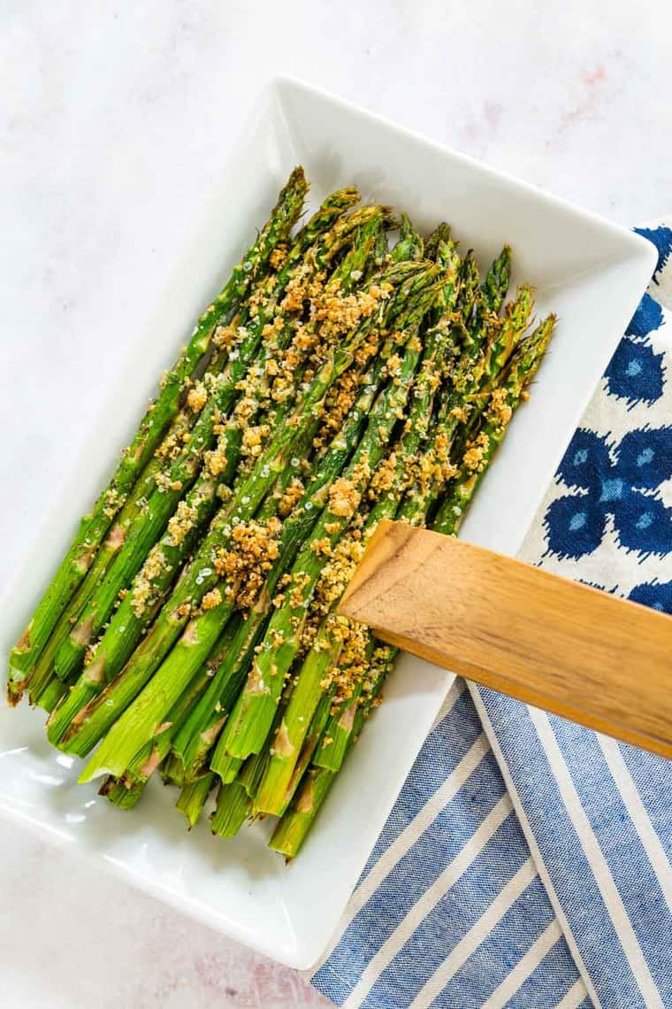 air fryer asparagus with parmesan being picked up from white rectangular plate with wooden tongs