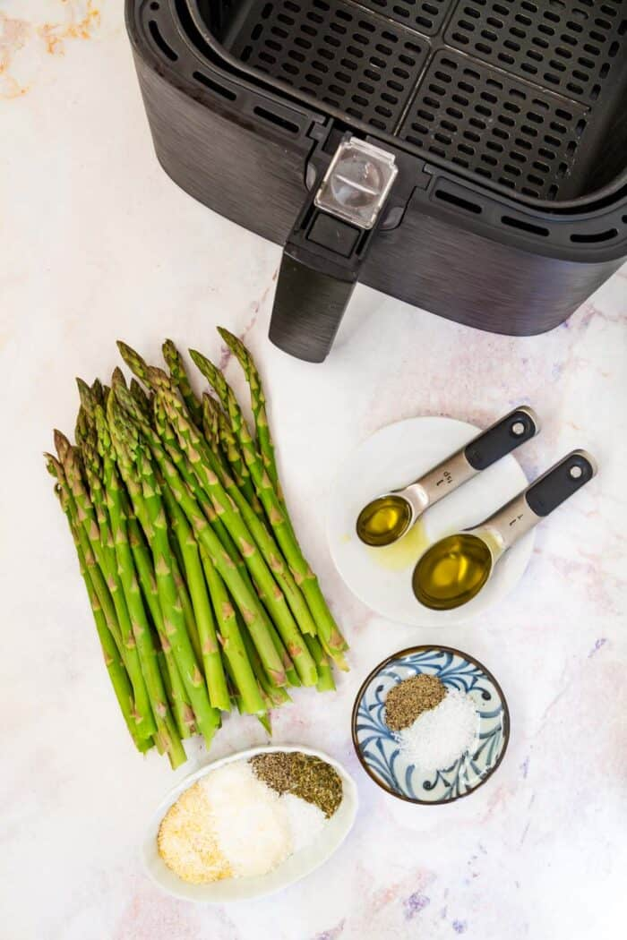 An air fryer, raw asparagus, a teaspoon and a tablespoon of olive oil, a small bowl of salt and pepper, and a ramekin with salt, pepper, cornmeal, parmesan cheese, and dried herbs on a marble tabletop