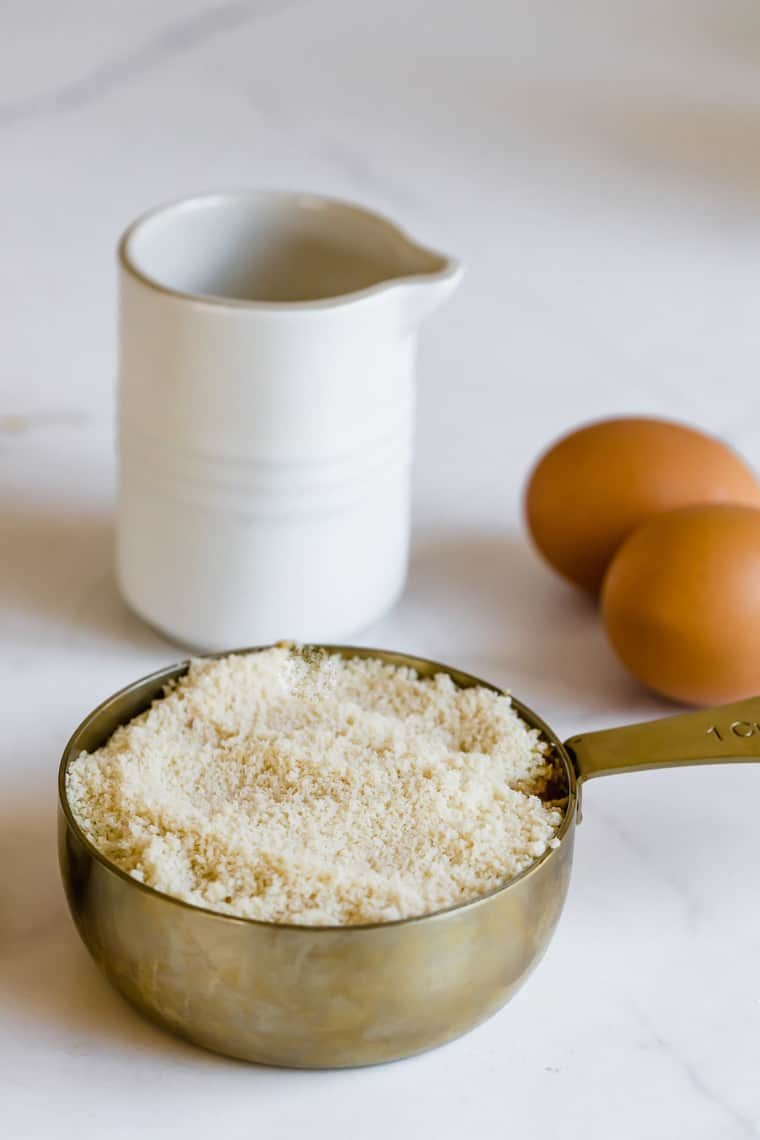 Almond Flour in a Metal Measuring Cup Next to Two Eggs and a Dish of Syrup