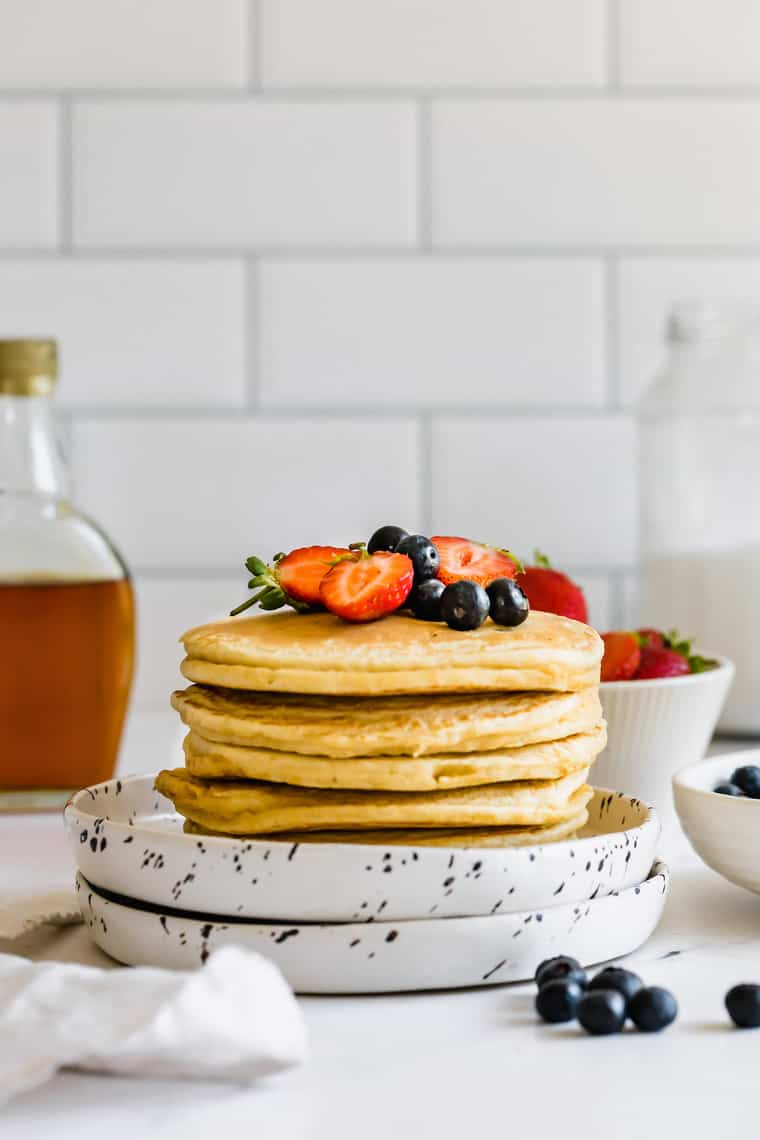 Almond Flour Pancakes Stacked on a Plate with Fresh Berries on Top