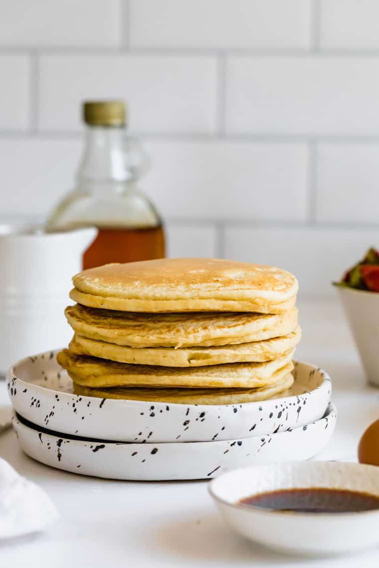 A Pile of Homemade Pancakes on Top of Two Stacked Black and White Plates