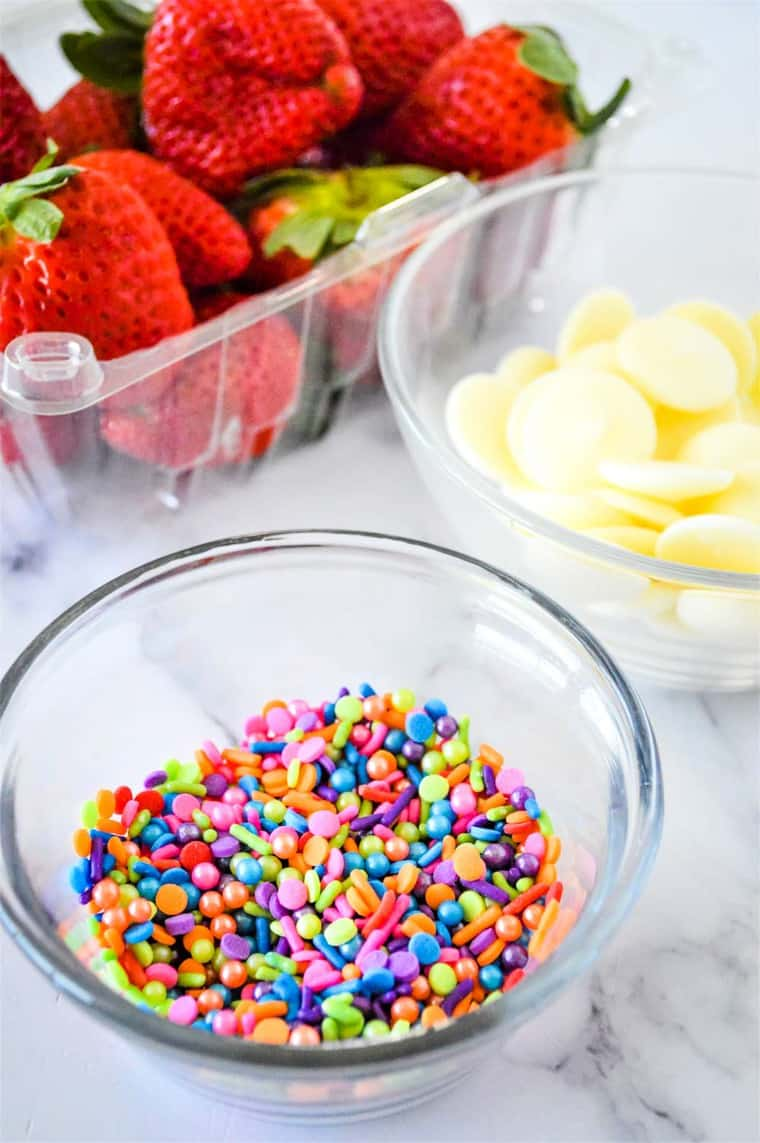 A container of fresh strawberries, a bowl of rainbow sprinkles, and a bowl of white chocolate candy melts