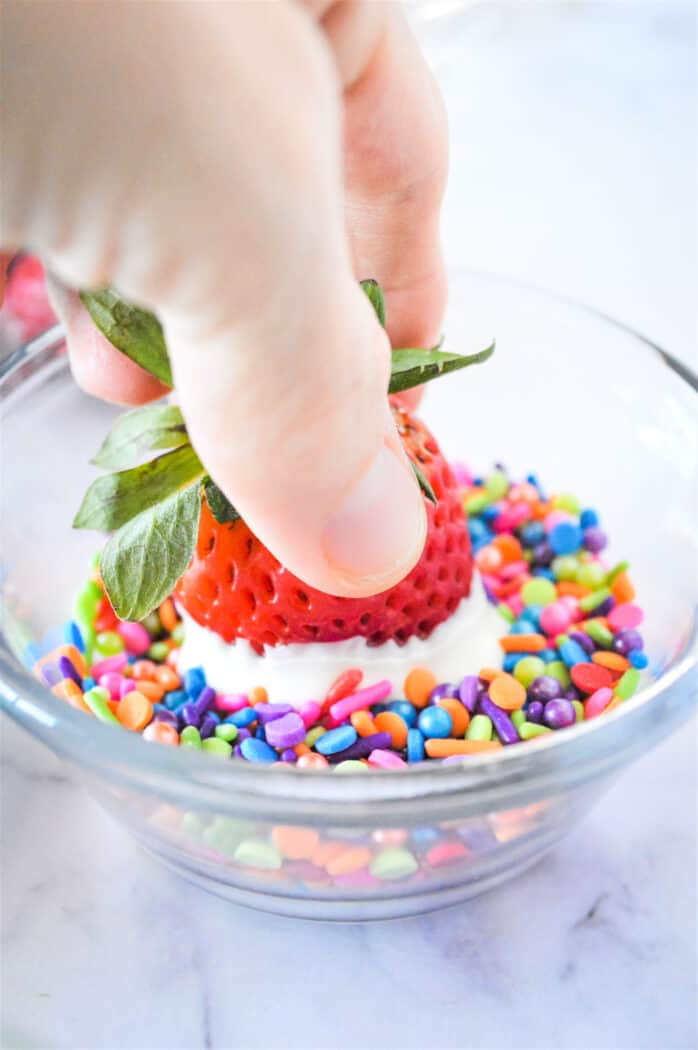 dipping a white chocolate covered strawberry into a bowl of rainbow sprinkles