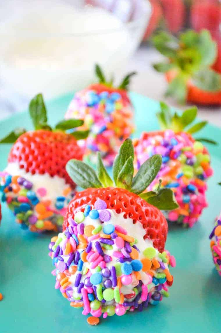 A turquoise plate with white chocolate strawberries dipped in sprinkles