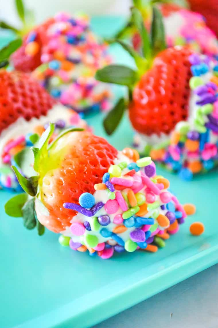 white chocolate strawberries covered in rainbow sprinkles on a turquoise plate