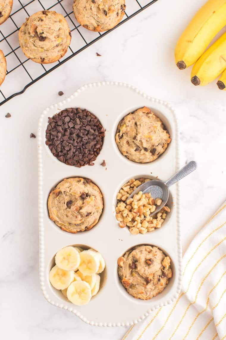 three baked muffins in a ceramic muffin pan with chocolate chips, walnuts, and bananas in the other cups