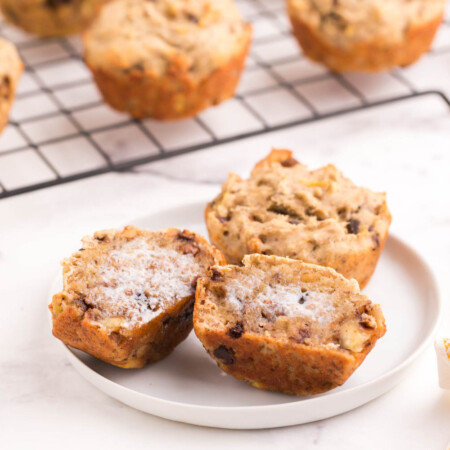 two gluten free banana chocolate chip muffins on a plate, one cut in half and buttered