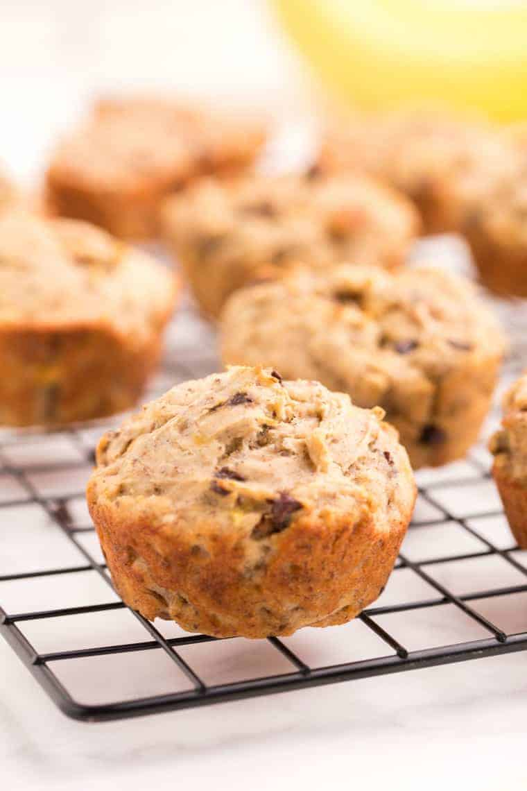 One gluten free banana chocolate chips muffin on a wire cooling rack with more behind it on the rack