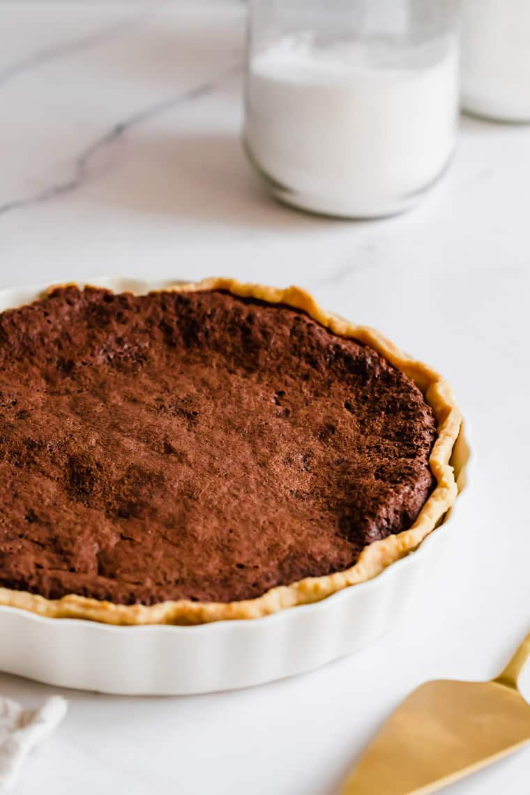 A Baked Chocolate Chess Pie on a White Marble Counter with a Glass of Milk