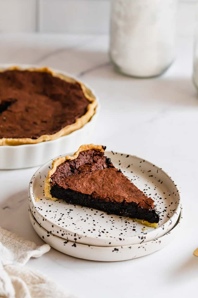 A Piece of Chocolate Pie on a Plate with the Full Chess Pie in the Background