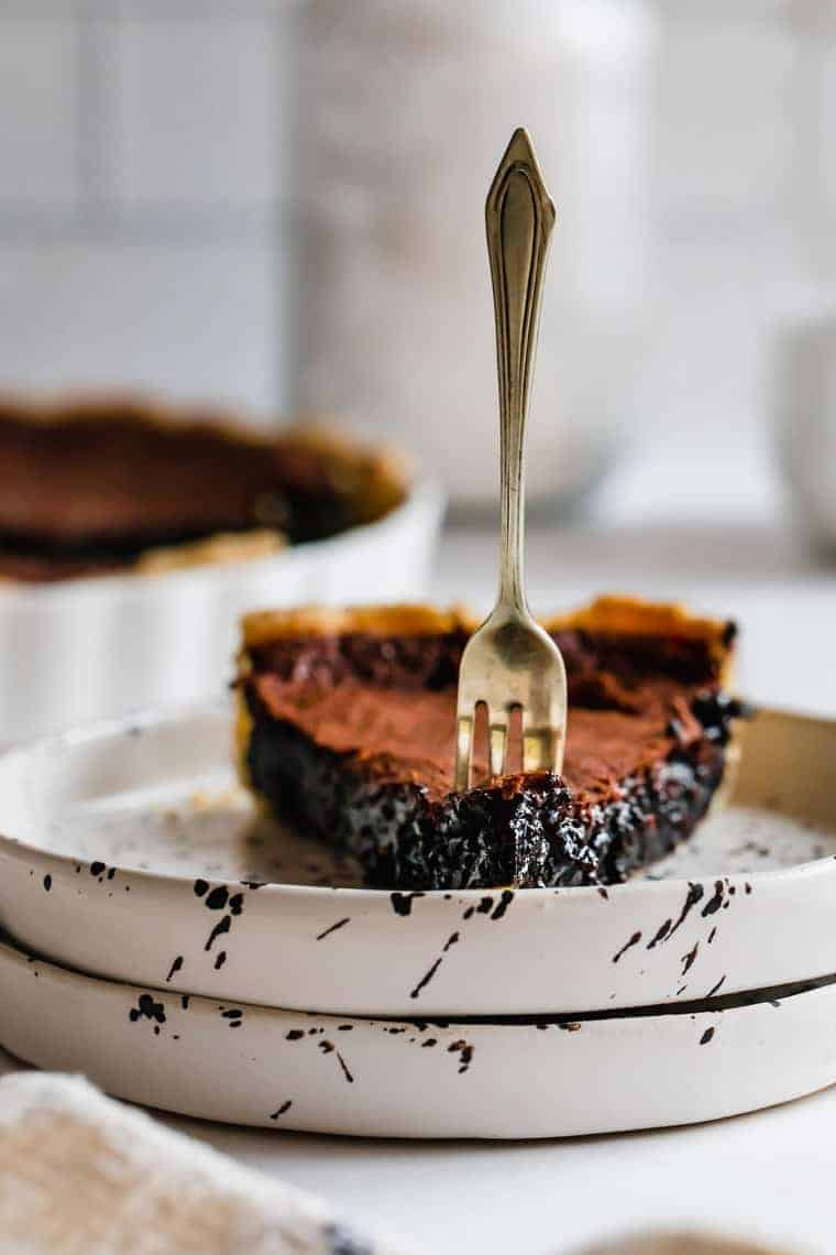 Two Stacked Plates Holding a Slice of Chocolate Chess Pie with a Fork Stuck Into it