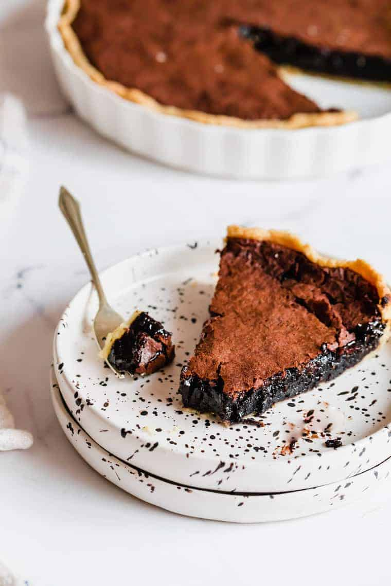 A Piece of Chocolate Chess Pie on a Plate With One Bite on a Fork