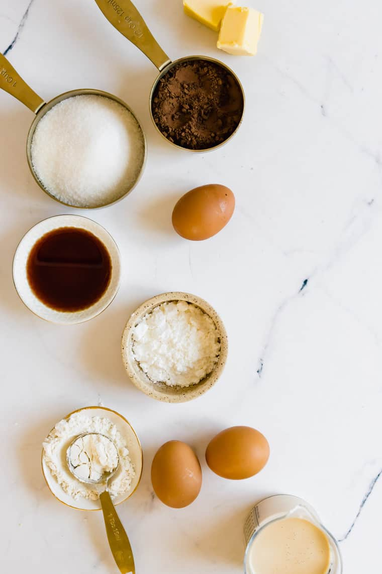 Three Eggs, Measuring Cups Filled with Cocoa Powder and Sugar, and the Rest of the Pie Ingredients on a Countertop