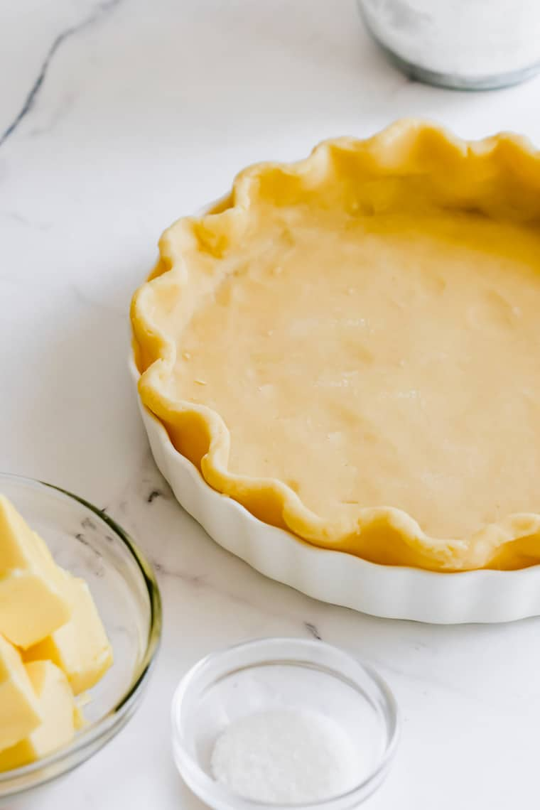 A Baked Pie Crust Beside a Dish of Butter and a Dish of Salt