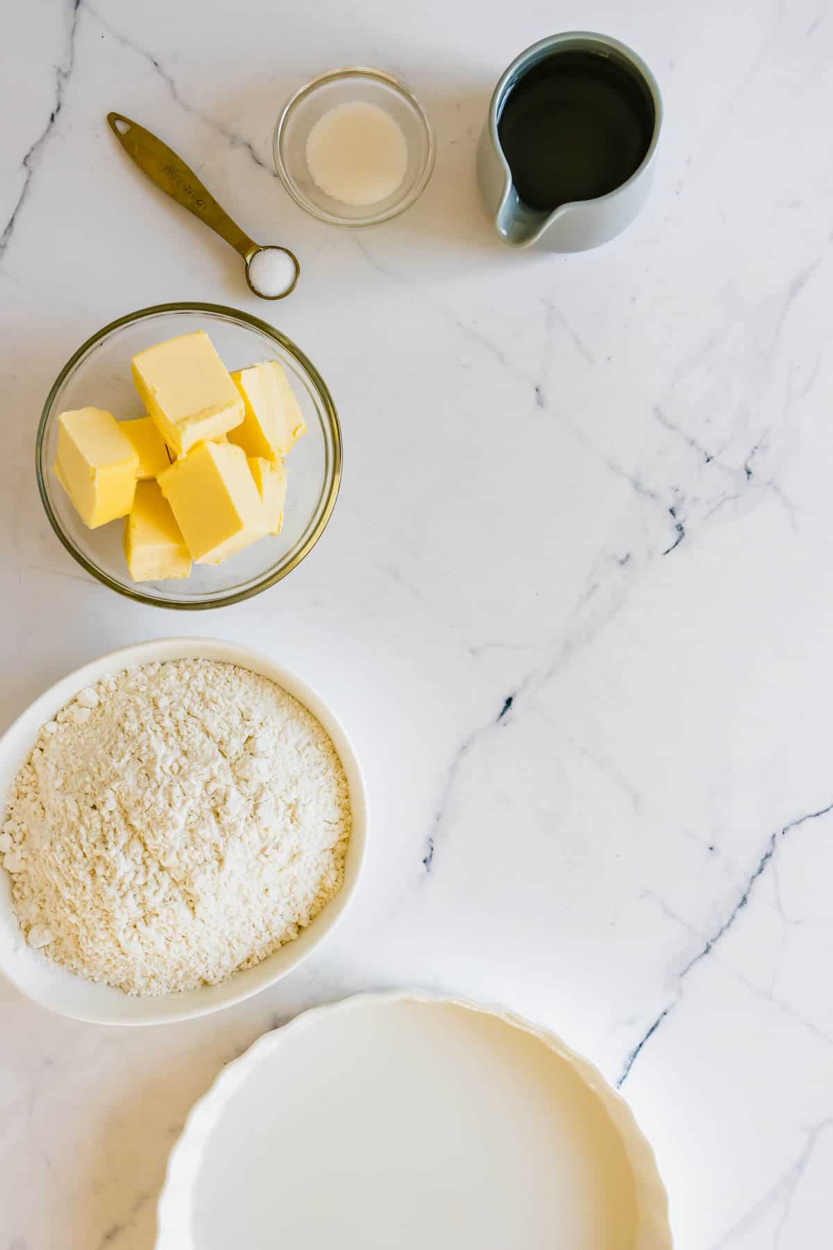 A Pie Dish, Cubed Butter, Gluten-Free Flour and the Rest of the Pie Crust Ingredients on a White Surface